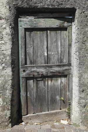 fanlight: an old wooden door in a valley in italy