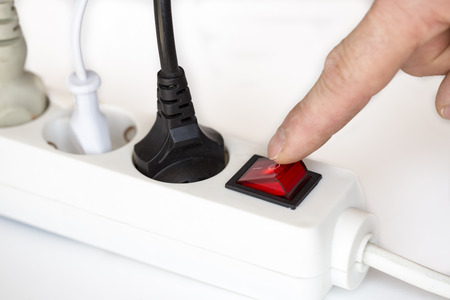 switch off with finger on white electric device