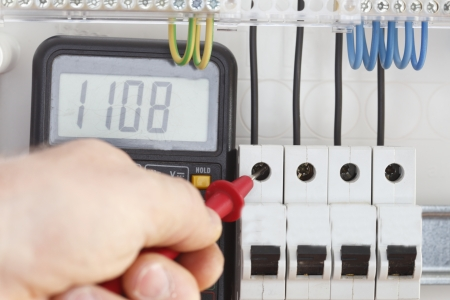 Multimeter, tester on work with electrical circuit photo