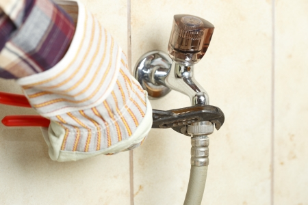 watertap: plumber is working with tool on water-tap Stock Photo