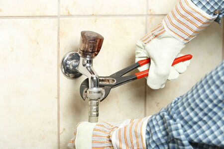 watertap: work man is fixing a water-tap with tool