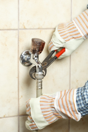 watertap: worker is fixing a water-tap with tool