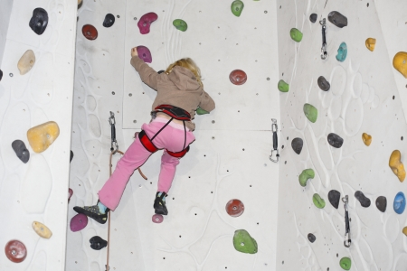 young girl is climbing on indoor wall photo