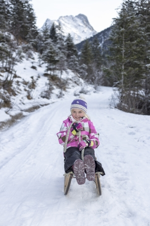 girl have fun on sledge in winter in the alps photo