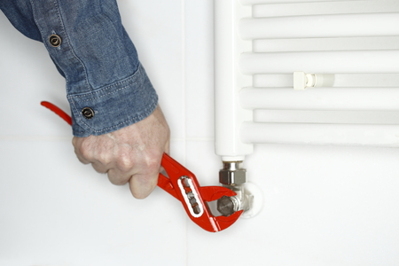 workman is working on heating in bathroom Standard-Bild