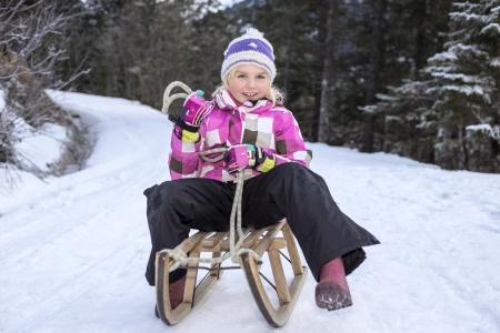 girl have fun on sledge in winter photo