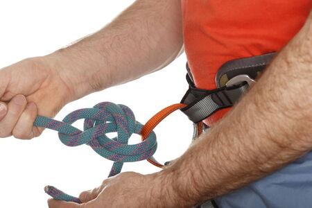 climber is binding a knot on belt photo