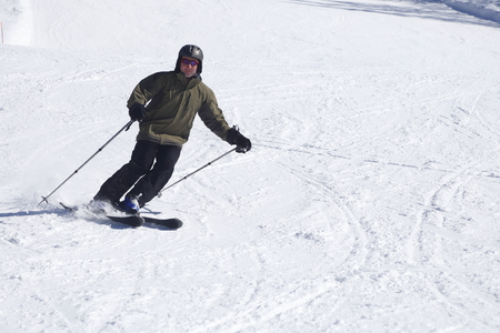 man is carving on white ski slope photo