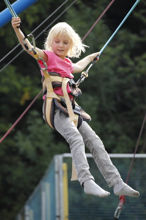 young girl have fun with jumping bungee photo
