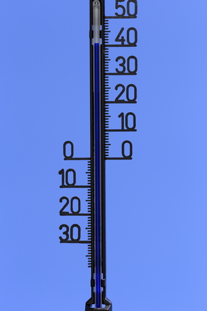 thermometer with high temperature on blue background photo