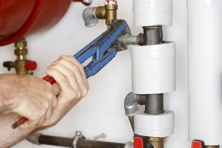 man is screwing on heating pipes with gripper
