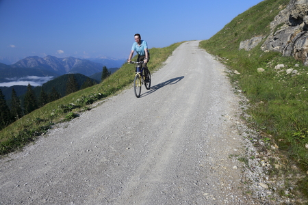 off road biking: biker is driving down on a street in the mountains Stock Photo