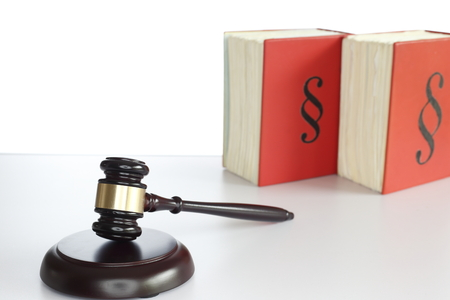 wooden gavel and books on grey table with white background photo