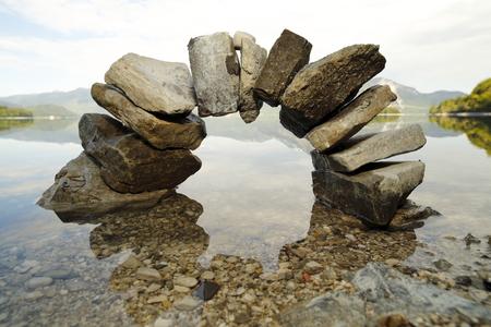 背景にある湖と大きな石の弓