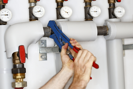 worker is fixing a pipe on a heating