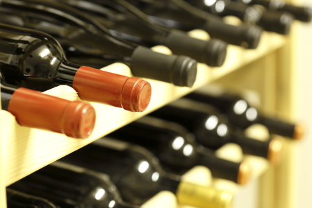 row of wine bottles in a wooden stack photo