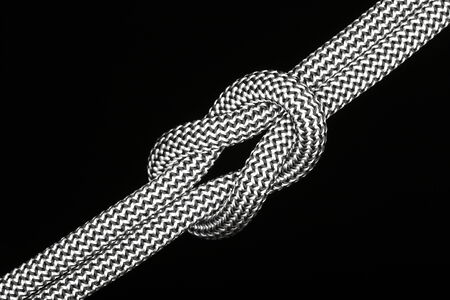 quadruple: cross knot with rope on black background