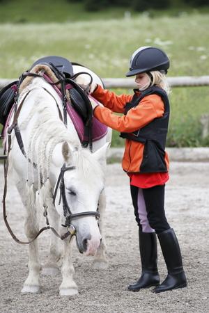 jong meisje met kleine witte paard buitenshuis