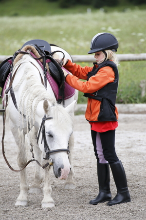 young girl with white little horse outdoors Standard-Bild