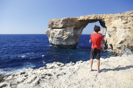 boy in front of famous stone arch of Gozo island  photo