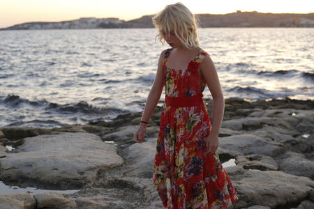 girl is walking along the coast on evening photo