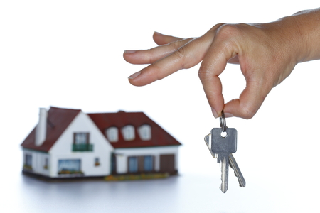 keyholder: hand is holding keys in background a house Stock Photo