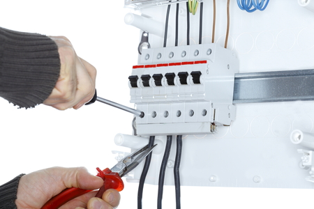 worker is screwing on a distribution board photo
