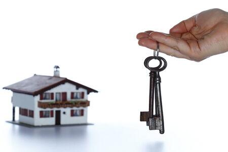 keyholder: hand and house keys on white background