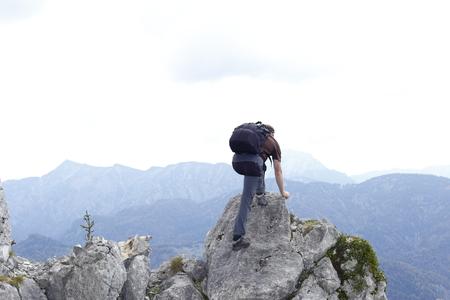 man is climbing up a mountain peak Banco de Imagens