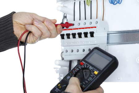 distribution board: worker with electrical tester is working on distribution board