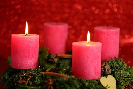 two candles with flame and red background photo