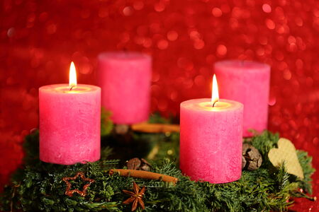 two pink candles with flame and red background photo