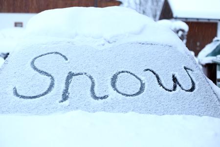 snowy windscreen with lettern on car in winter photo