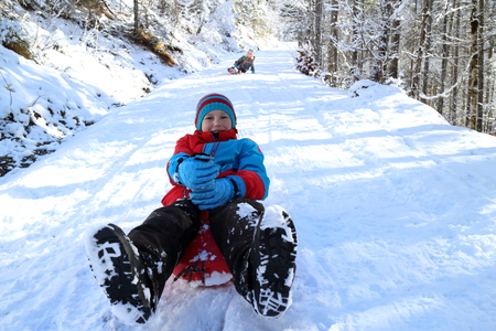 children have fun with sledges in winter landscape photo