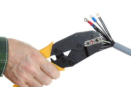 cable cutter: electrician is crimping a plug on wire with white background