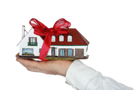 hand is holding house model as gift photo