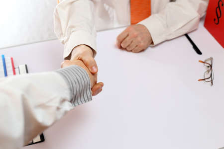 businessteam: two business persons are handshaking in office