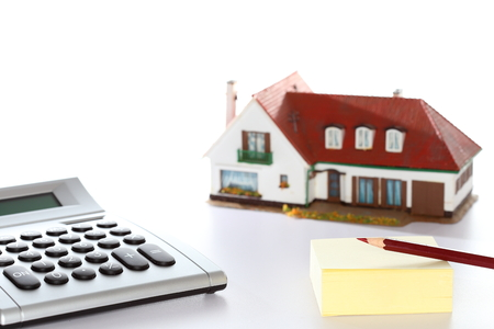 lender: calculator and house model with pen and paper Stock Photo