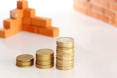 economic rent: stack of coins and stack of bricks