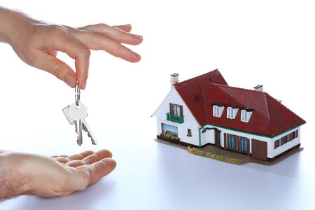 keyholder: hands and key with house model in background Stock Photo