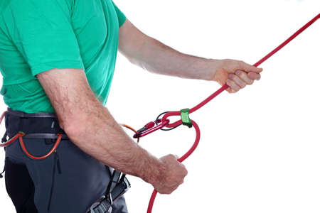 belaying: mountaineer is belaying with rope on white background