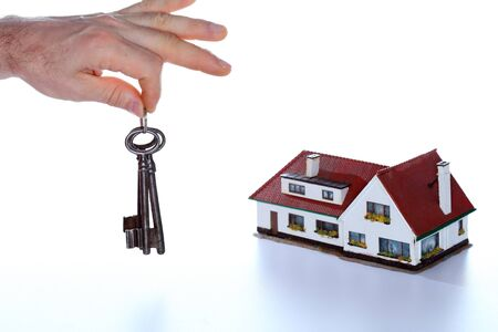 keyholder: keys in hand with house model in background