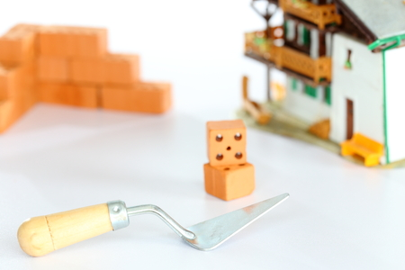 redbrick: tools and bricks in front of a house model Stock Photo