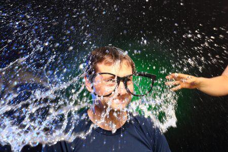 man s: colorful watersplash on man s head with glasses Stock Photo