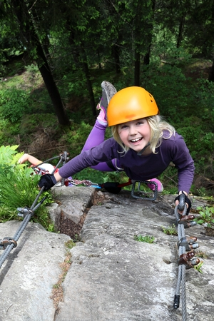 smiling girl enjoy climbing up on fixed rope route