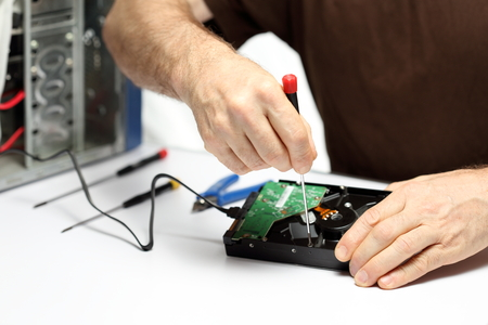 hardware: man is repairing computer hardware on a desk