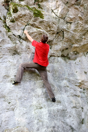 man is practicing climbing on a rock wall