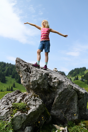 young girl is standing on a rock in alps