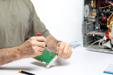 screwing: computer worker is screwing a computer component