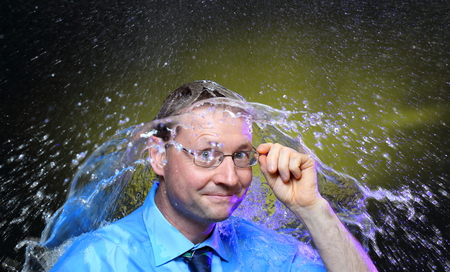 rain wet: business man with glasses is showering with water Stock Photo